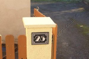 Customer photo of Art-Deco granite number sign screw fixed to pillar. This is somewhere in France!