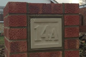 Customer photo of Indian sandstone number sign set into brick pillar. the number carved in-relief. The font Engravers times.