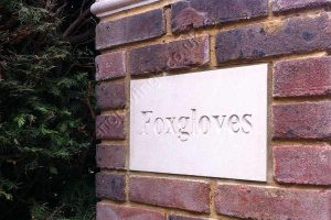 Customer photo. Sandstone house name sign set into brickwork of driveway pillar. The font is Times bold, deep engraved and left natural.