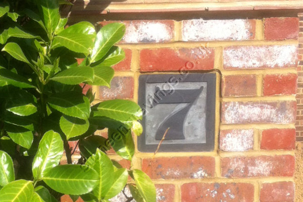 Customer photo of Welsh slate number sign set into brick pillar. the number carved in-relief. The font Timpani.
