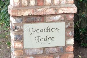 Customer photo. Sandstone house name sign set into brickwork of driveway pillar. The font is Chancery, deep engraved and left natural.