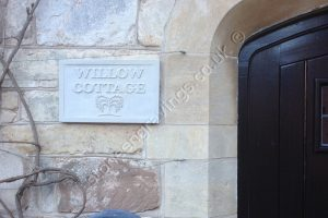 Customers photo: Sandstone house sign carved in-relief using our Willow tree motif and Engravers Times font.