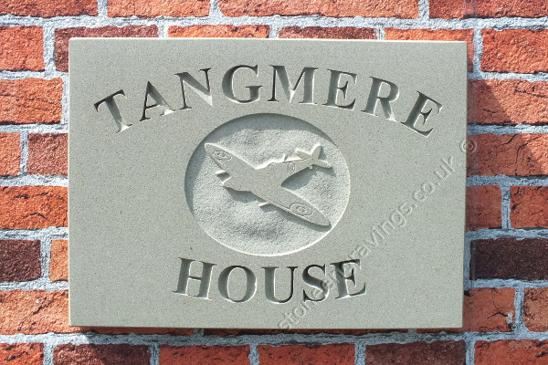 """Tangmere House. York stone house sign with Spitfire carved in-relief into an oval panel. The font is """"Times Roman""""."""