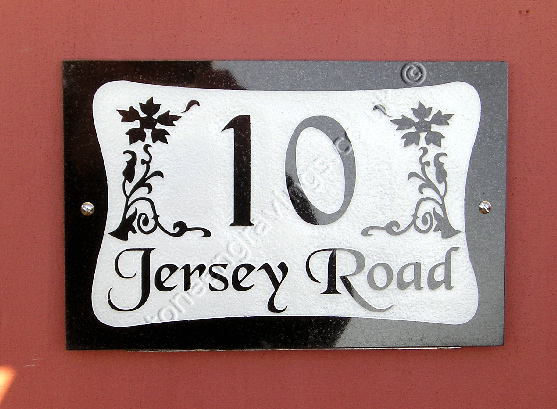 Rhinefield Farm, black granite house sign carved in-relief with Cancery Font. In this example the background has been painted white to further highlight the lettering.