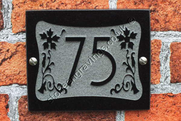 Art-Nouveau style house number carved in-relief. Black granite, Andes font.
