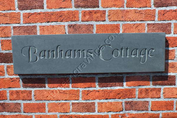 Banhams Cottage, house sign in Welsh slate. Font Chancery Gothic, lettering left natural (unpainted).