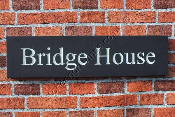 Bridge house,, house sign in Welsh slate. Font Times Roman title-case, lettering highlighted in white.