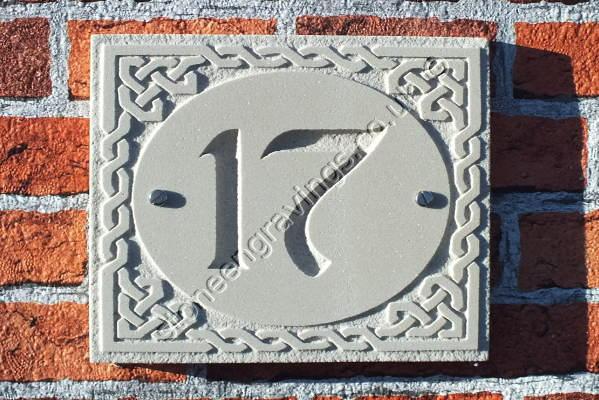 Celtic design house number sign. Incised number in Chancery font set into a celtic knotwork oval border. Sandstone.