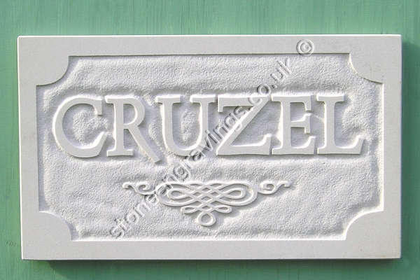 CRUZEL sandstone house sign, carved in-relief. Flourish motif. Font unknown.