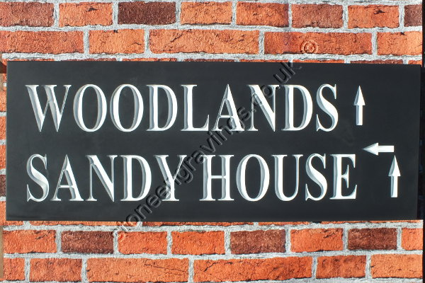 Woodlands, house sign in Welsh slate. Font Times Roman modified, lettering highlighted in white.