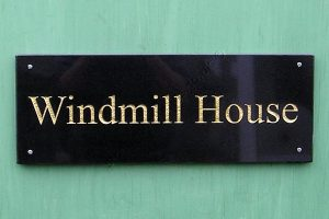 Windmill house, house sign in Black Absoluto granite Times Roman standard title-case font engraved and finished gold.