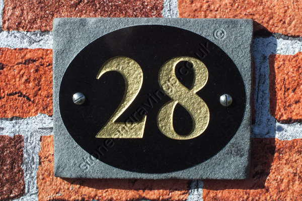 Polished granite oval set on a rocky border. House number engraved and painted gold.