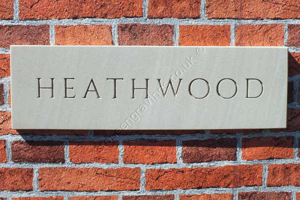 Heathwood cream sandstone house sign. Chinzel decorative lowercase font with modified spacing. Lettering left natural (unpainted)