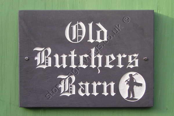 Old Butchers Barn, house sign in Welsh slate. Golfer returning home motif carved in-relief in an oval panel. Old English font . Engraved and filled white.