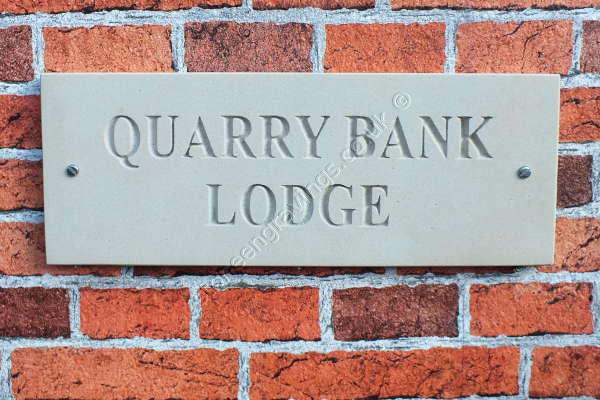 Quarry Bank Lodge sandstone house sign. Times standard font uppercase. Lettering left natural (unpainted)