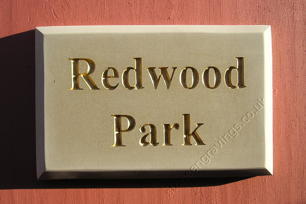 Redwood Park, Yorkstone with chamfered edge. lettering Times bold painted gold.