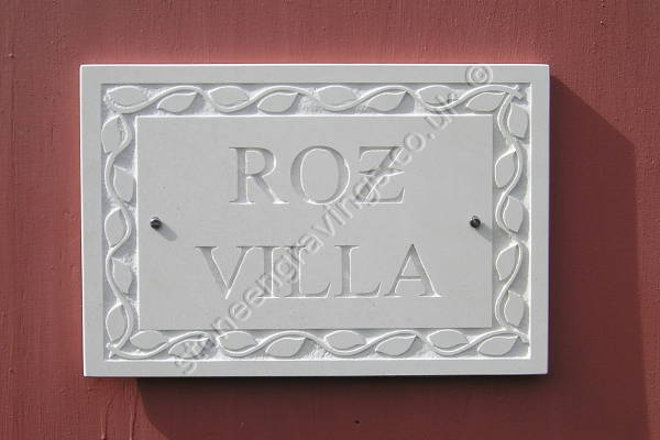 Roz villa house sign. Cream sandstone Modified Times font. Leaf edge border carved in-relief.