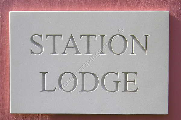 Station Lodge sandstone house sign. Times standard font uppercase. Lettering left natural (unpainted)