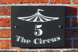 "Welsh slate house number sign with Circus Artwork. The font is ""Poster Bodoni""."