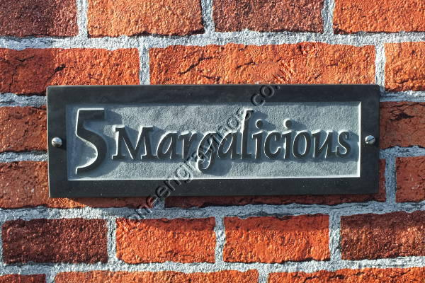 "Margalicious house sign in Welsh slate carved in-relief. The font is ""Dolphin""."