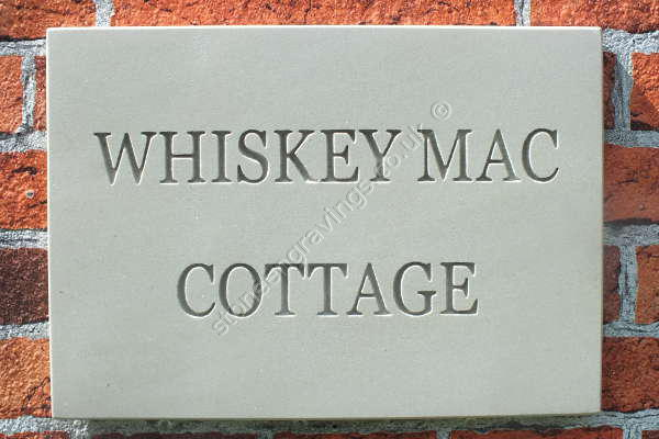 Whisky Mac sandstone house sign. Times standard font uppercase, deep engraved for high visibility. Lettering left natural (unpainted).