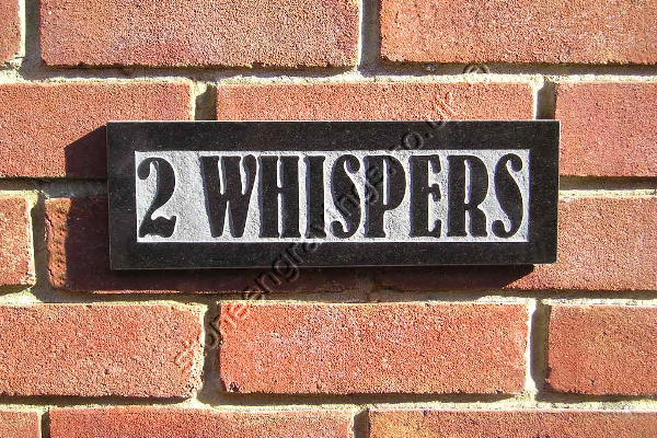 Whispers, black granite house sign carved in-relief with Bernhard Font.